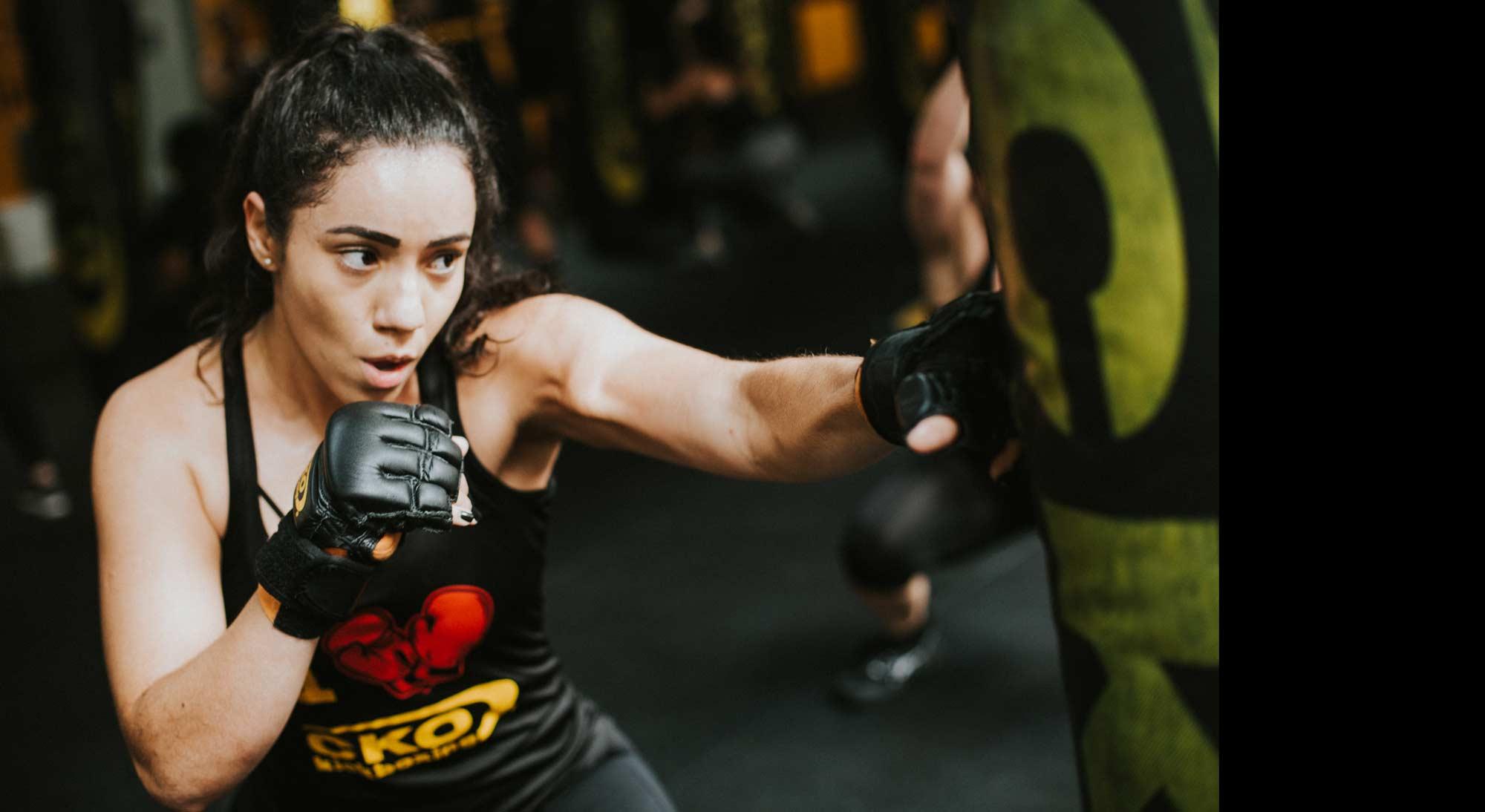 A woman hitting heavy punching bag.