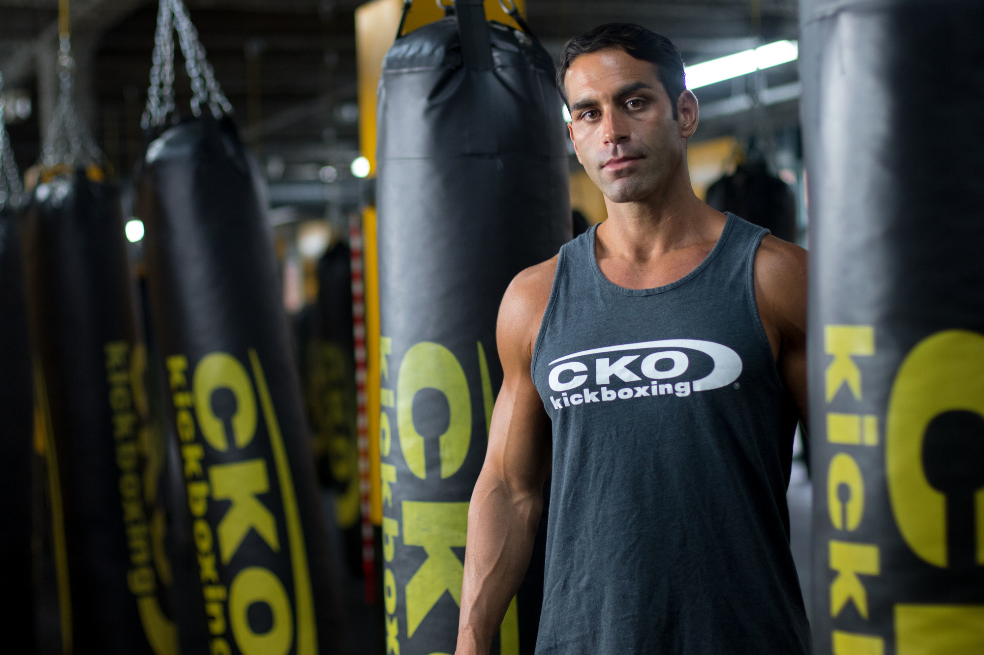 Personal trainer standing behind punching bag